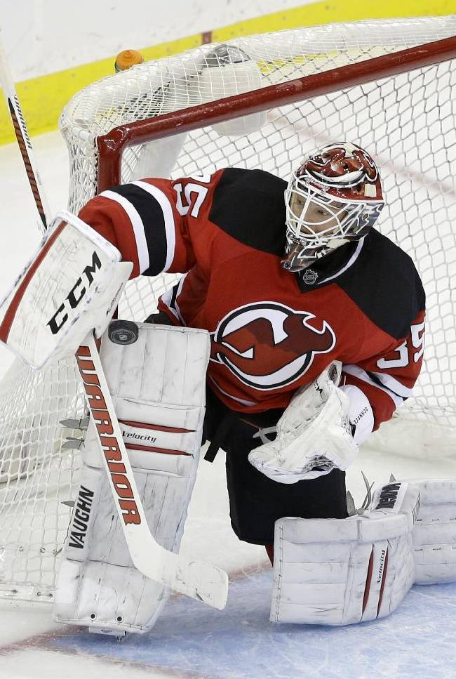 New Jersey Devils goalie Cory Schneider (35) makes a stick-save during the third period of an NHL hockey game against the San Jose Sharks, Sunday, March. 2, 2014, in Newark, N.J. The Sharks won 4-2