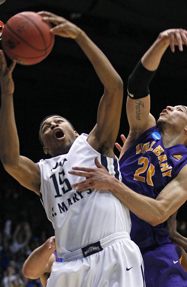 Mount St. Mary's forward Gregory Graves (15) pulls a rebound away from Albany forward Gary Johnson in the first half of a first-round game of the NCAA college basketball tournament, Tuesday, March 18, 2014, in Dayton, Ohio