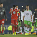 Wolfsburg goalkeeper Diego Benaglio from Switzerland, center left in orange, makes his way with teammates to applaud supporters after their team's 4-1 loss to Everton in their Europa League Group H soccer match at Goodison Park Stadium, Liverpool, England