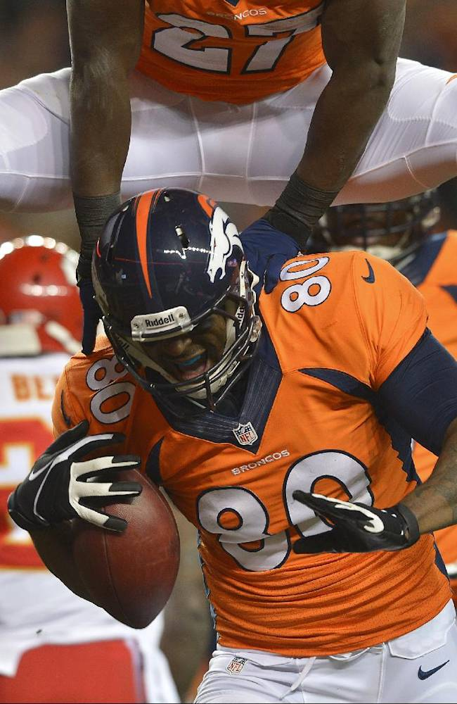 Denver Broncos running back Knowshon Moreno (27) leaps over Denver Broncos tight end Julius Thomas (80) after Thomas caught a touchdown pass against the Kansas City Chiefs in the first quarter of an NFL football game, Sunday, Nov. 17, 2013, in Denver