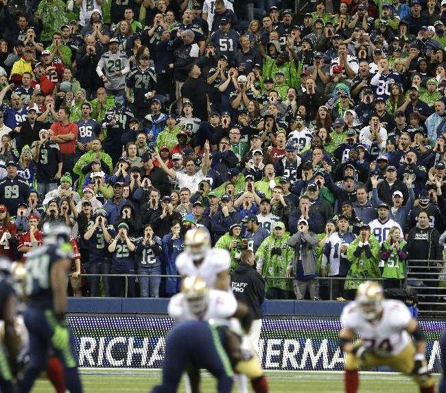 Seattle Seahawks fans yell during a San Francisco 49ers possession in the first half of an NFL football game, Sunday, Sept. 15, 2013, in Seattle. Fans were attempting to set a Guinness World Record for fan noise at an athletic event during the game