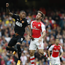 Hull City's Abel Hernandez, left, jumps and misses the ball with Arsenal's Nacho Monreal during the English Premier League soccer match between Arsenal and Hull City at the Emirates stadium in London Saturday, Oct.18, 2014
