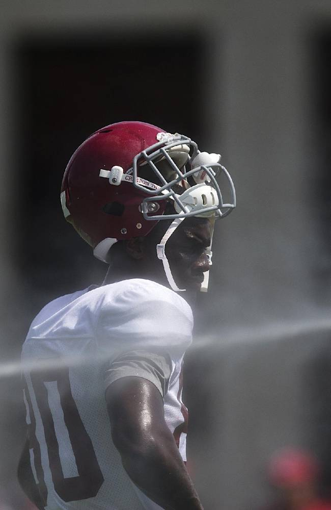Alabama Crimson Tide wide receiver Raheem Falkins (80) stands in the stream of water to cool down during an NCAA college football practice at BryantDenny Stadium on Tuesday, Aug. 12, 2014, in Tuscaloosa, Ala