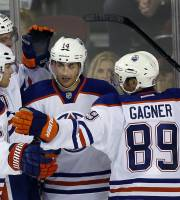 Edmonton Oilers' Jordan Eberle, center, celebrates his game-winning goal with teammates, from left to right, Philip Larsen, from Denmark, Martin Marincin, from Slovakia, and Sam Gagner, during third-period NHL preseason hockey game action in Calgary, Alberta, Saturday, Sept. 14, 2013. The Oilers won 3-2.(AP Photo/The Canadian Press, Jeff McIntosh)