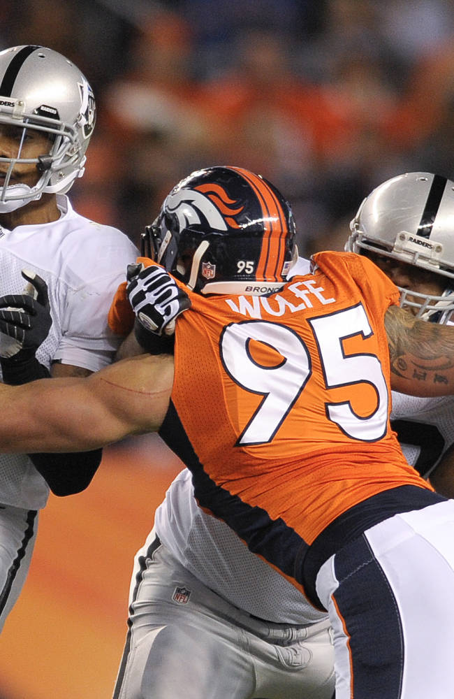 Oakland Raiders quarterback Terrelle Pryor (2) is hit by Denver Broncos defensive end Derek Wolfe (95) after throwing a pass in the second quarter of an NFL football game, Monday, Sept. 23, 2013, in Denver