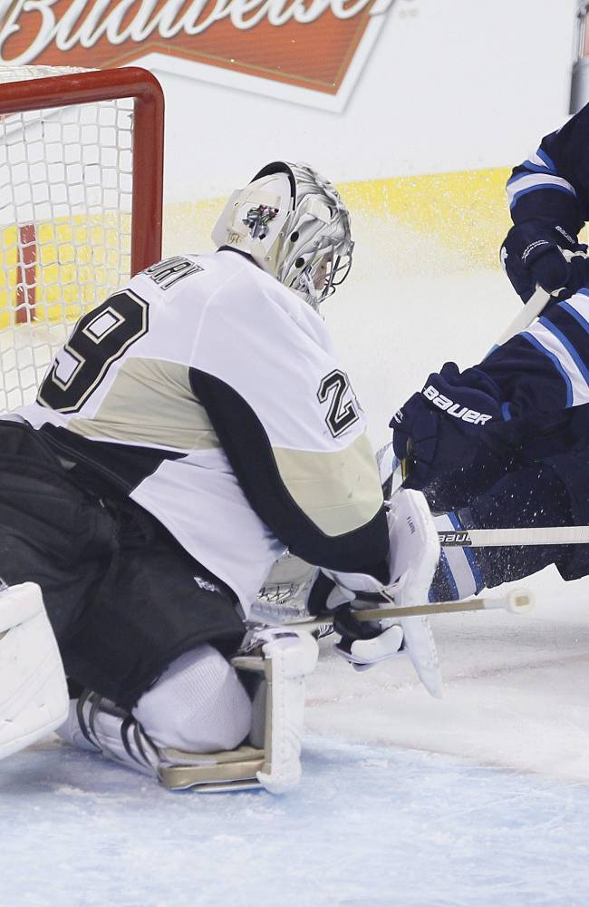 Pittsburgh Penguins goaltender Marc-Andre Fleury (29) stops the shot from Winnipeg Jets' Jim Slater (19) as Penguins' Rob Scuderi (4) helps defend during the first period of an NHL hockey game in Winnipeg, Manitoba, on Thursday, April 3, 2014