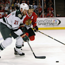 Minnesota Wild's Kyle Brodziak (21) is defended by Chicago Blackhawks' Brent Seabrook in the first period of an NHL hockey game in Chicago, Thursday, April 3, 2014 The Associated Press