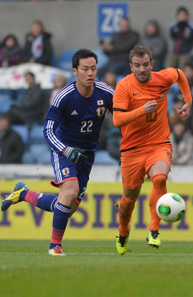 Japan's Maya Yoshida, left, challenges Rafael van der Vaart from the Netherlands during a friendly soccer match at the Fenix stadium in Genk, Belgium on Saturday, Nov. 16, 2013
