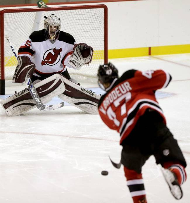 William Brodeur, bottom, son of New Jersey Devils' goalkeeper Martin Brodeur, takes a shot against his twin brother, goalkeeper Jeremy Brodeur, during tge Devils' rookies NHL hockey camp, Tuesday, July 15, 2014, in Newark, N.J. The 17-year-old siblings are participating along with their older brother, Anthony Brodeur, 19, during camp