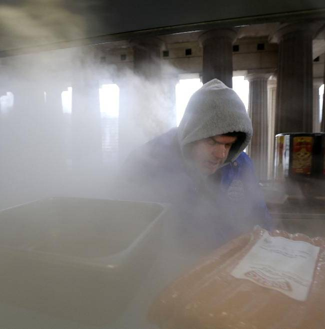 Food vendor Dean Postma is engulfed in steam as he prepares bratwursts before an NHL Stadium Series hockey game at Soldier Field between the Chicago Blackhawks and the Pittsburgh Penguins on Saturday, March 1, 2014, in Chicago