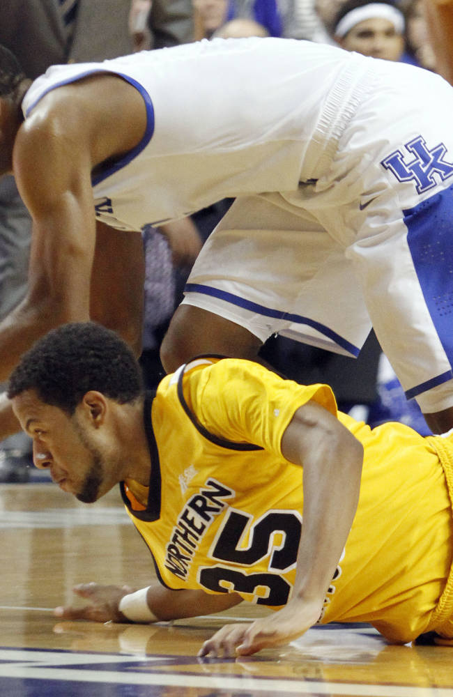 Kentucky's Aaron Harrison, top, gathers up a loose ball next to Northern Kentucky's Deontae Cole (35) during the first half of an NCAA college basketball game on Sunday, Nov. 10, 2013, in Lexington, Ky