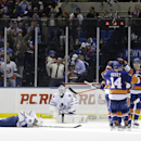 Toronto Maple Leafs goalie Jonathan Bernier (45) and Tim Gleason (8) react as New York Islanders celebrate a Lubomir Visnovsky goal in overtime of an NHL hockey game Thursday, Feb. 27, 2014, in Uniondale, N.Y. The Islanders won 5-4 The Associated Press