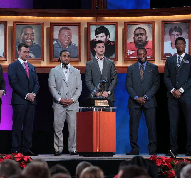 Heisman Trophy finalists, from left, Northern Illinois quarterback Jordan Lynch, Texas A&M quarterback Johnny Manziel, Auburn running back Tre Mason, Alabama quarterback AJ McCarron, Boston College running back Andre Williams and Florida State quarterback Jameis Winston stand behind the trophy before it was announced that Winston is this year's trophy winner at the Best Buy Theater, Saturday, Dec. 14, 2013 in New York