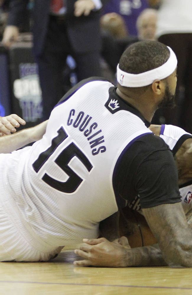 Sacramento Kings' DeMarcus Cousins, center, and Isaiah Thomas, right, dive to the floor for the ball with Phoenix Suns guard Goran Dragic, left, of Slovenia, during the  fourth quarter of an NBA basketball game in Sacramento, Calif., Tuesday, Nov. 19, 2013.  The Kings won 107-104