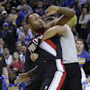 Portland Trail Blazers' Mo Williams is restrained by a referee after fighting with Golden State Warriors' Andrew Bogut during the second half of an NBA basketball game Saturday, Nov. 23, 2013, in Oakland, Calif. Trail Blazers Wesley Matthews, Mo Williams,
