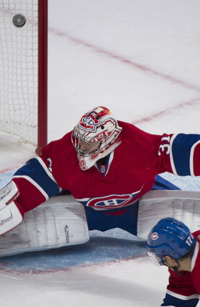 Montreal Canadiens' goaltender Carey Price is scored on by the Edmonton Oilers' Ladislav Smid  as Canadiens' Rene Bourque defends during the second period of an NHL hockey game in Montreal, Tuesday, Oct. 22, 2013