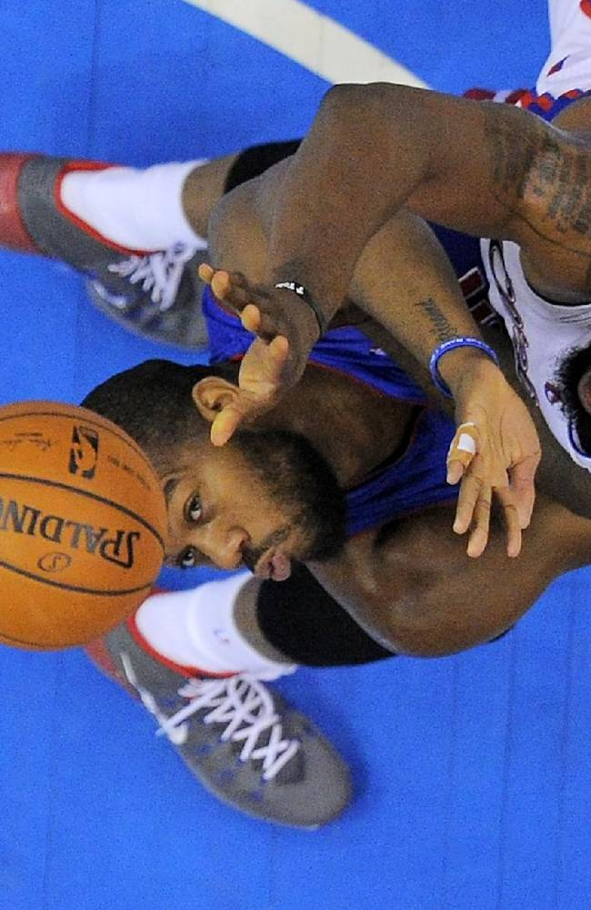 Los Angeles Clippers center DeAndre Jordan, right, shoots as Detroit Pistons forward Greg Monroe defends during the first half of an NBA basketball game, Saturday, March 22, 2014, in Los Angeles