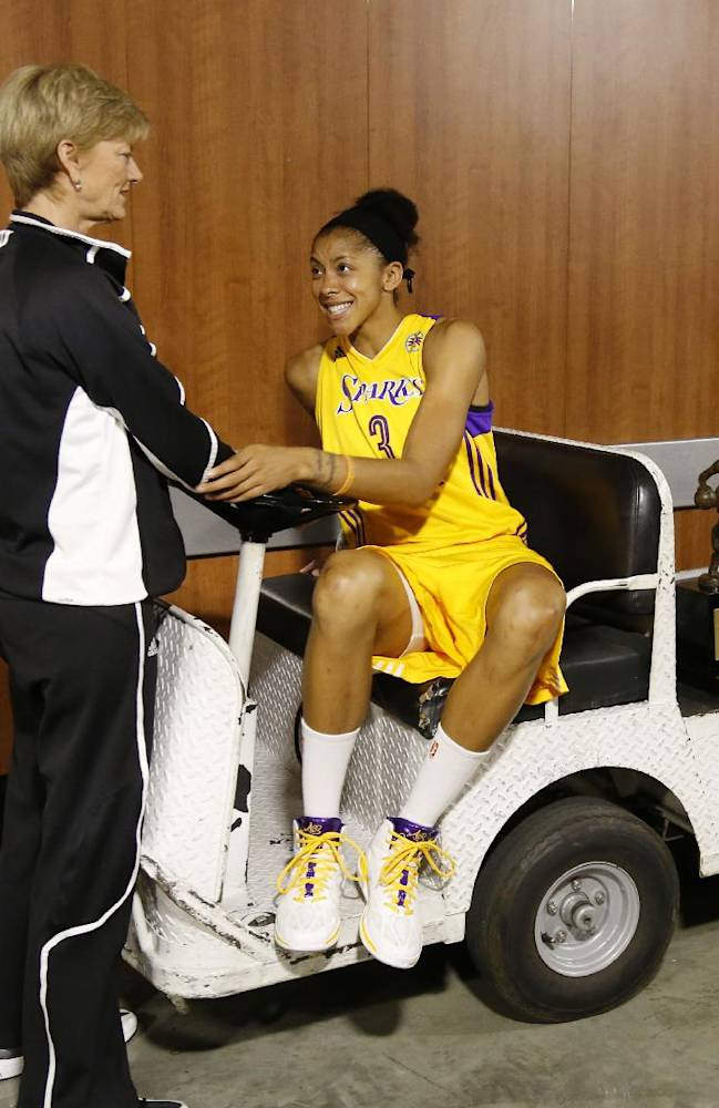 Los Angeles Sparks' forward Candace Parker, right, sits next to her WNBA MVP trophy on a cart as she talks with head coach Carol Ross outside the locker room before playing the Phoenix Mercury in the opener of their WNBA basketball Western Conference semifinal series on Thursday, Sept. 19, 2013, in Los Angeles