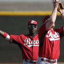 Cincinnati Reds second baseman Brandon Phillips, left, jokes with teammate Zack Cozart as the team practices fielding pop fly balls during a spring training baseball workout Thursday, Feb. 20, 2014, in Goodyear, Ariz The Associated Press