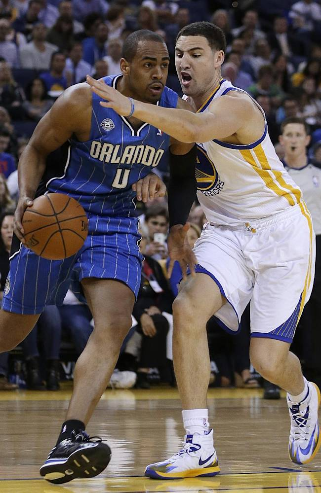 Orlando Magic guard Arron Afflalo, left, drives the ball against Golden State Warriors' Klay Thompson during the first half of an NBA basketball game Tuesday, March 18, 2014, in Oakland, Calif