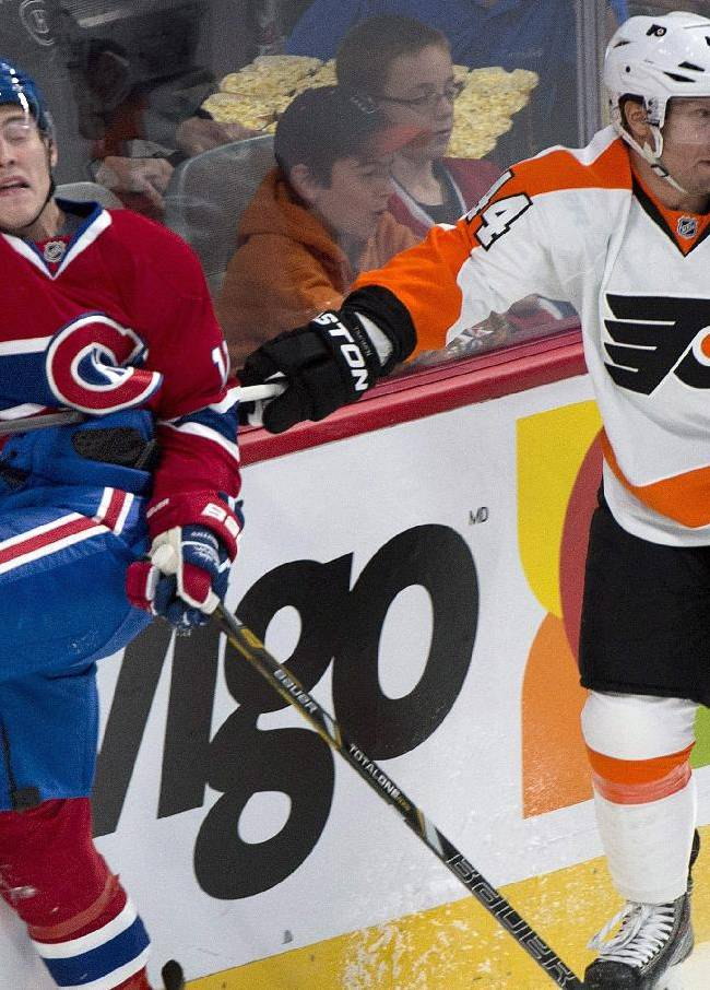 Philadelphia Flyers' Kimmo Timonen, right, gets his stick up on Montreal Canadiens' Brendan Gallagher during the second period of an NHL hockey game in Montreal, Saturday, Oct. 5, 2013