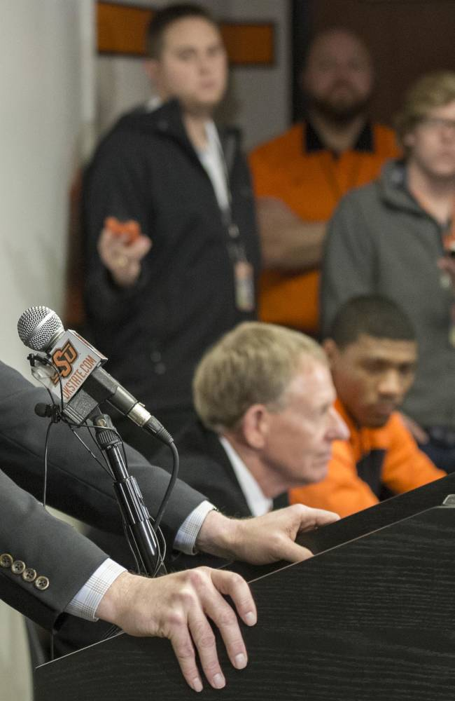 This photo provided by Oklahoma State University Athletics shows Oklahoma State basketball coach Travis Ford addressing the media at a news conference in Stillwater, Okla., Sunday, Feb. 9, 2014, in regard to player Marcus Smart shoving a fan during an NCAA college basketball game the day before. Smart was suspended for three games by the Big 12
