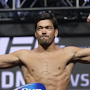 Lyoto Machida poses on the scale during a weigh-in for the UFC 175 mixed martial arts event at the Mandalay Bay, Friday, July 4, 2014, in Las Vegas. Machida is scheduled to fight Chris Weidman in a middleweight title bout on Saturday in Las Vegas. (AP Photo/John Locher)