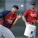 St. Louis Cardinals outfielder Matt Holliday, left, catches a tennis ball with his bare hand as hitting coach John Mabry watches during a drill at spring training baseball practice Friday, Feb. 21, 2014, in Jupiter, Fla The Associated Press