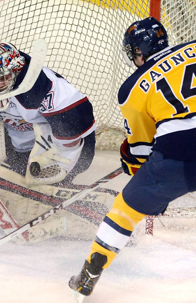 Saginaw Spirit goalie Jake Paterson, left, makes a save on Erie Otters' Brendan Gaunce in the first period of Game 2 of the Ontario Hockey League playoff game in Erie, Pa., on Saturday, March 22, 2014