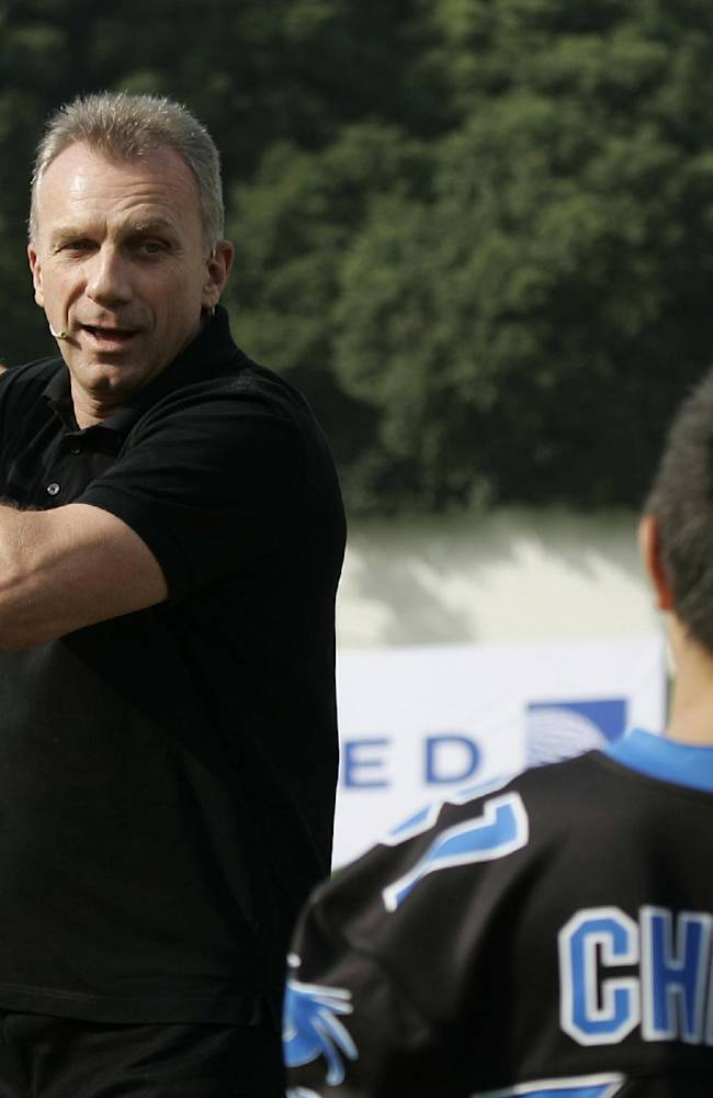 Former NFL football player Joe Montana, left, gives a lesson to children during an NFL promotional event in Shanghai, China, Saturday, Nov. 16, 2013. Montana is in China as a special guest for the University Bowl V Championship. (AP Photo)