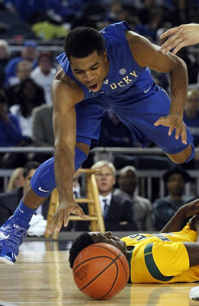 Kentucky guard Andrew Harrison reaches out for a loose ball after colliding with Baylor's Taurean Prince, bottom, on a drive to the basket in the second half of an NCAA college basketball game, Friday, Dec. 6, 2013, in Arlington, Texas. Harrison was assessed a foul on the play. Baylor upset Kentucky 67-62