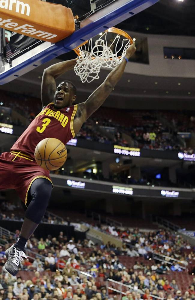 Cleveland Cavaliers' Dion Waiters, left, hangs on the rim after a dunk as Philadelphia 76ers' Tony Wroten trails during the first half of an NBA basketball game, Friday, Nov. 8, 2013, in Philadelphia