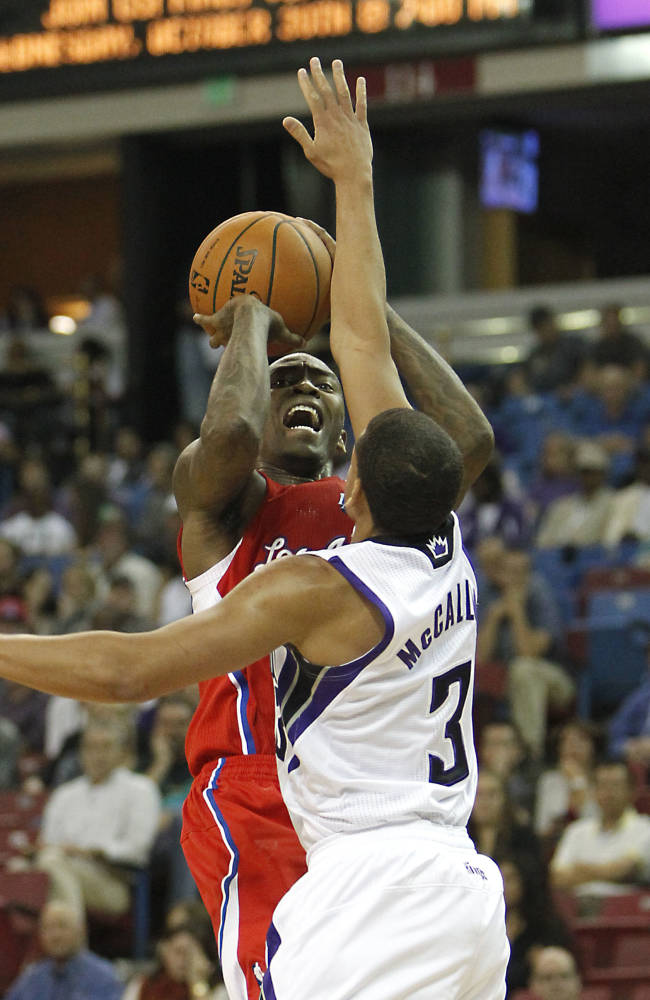 Los Angeles Clippers guard Jamal Crawford, left, shoots against Sacramento Kings guard Ray McCallum during the fourth quarter of an NBA preseason basketball game in Sacramento, Calif., Monday, Oct. 14, 2013.   The Kings won 99-88