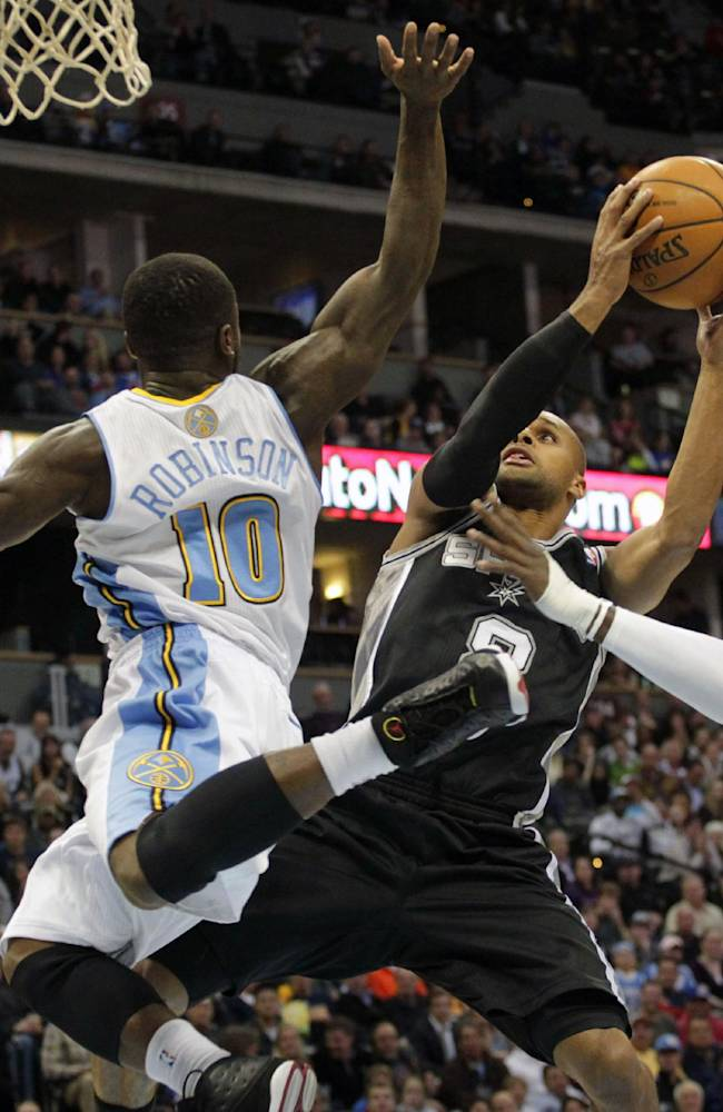 San Antonio Spurs guard Patty Mills (8) drives against Denver Nuggets guard Nate Robinson (10) and Nuggets forward J.J. Hickson (7) in the first quarter of a basketball game in Denver on Tuesday, Nov. 5,