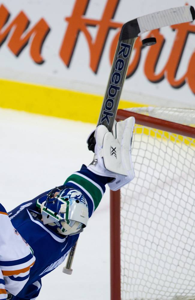 Vancouver Canucks' goalie Roberto Luongo, back, reaches up with his stick and swats the puck out of the air to keep it from entering the net as Edmonton Oilers' Matt Hendricks watches during third period NHL hockey action in Vancouver, British Columbia, on Monday Jan. 27, 2014