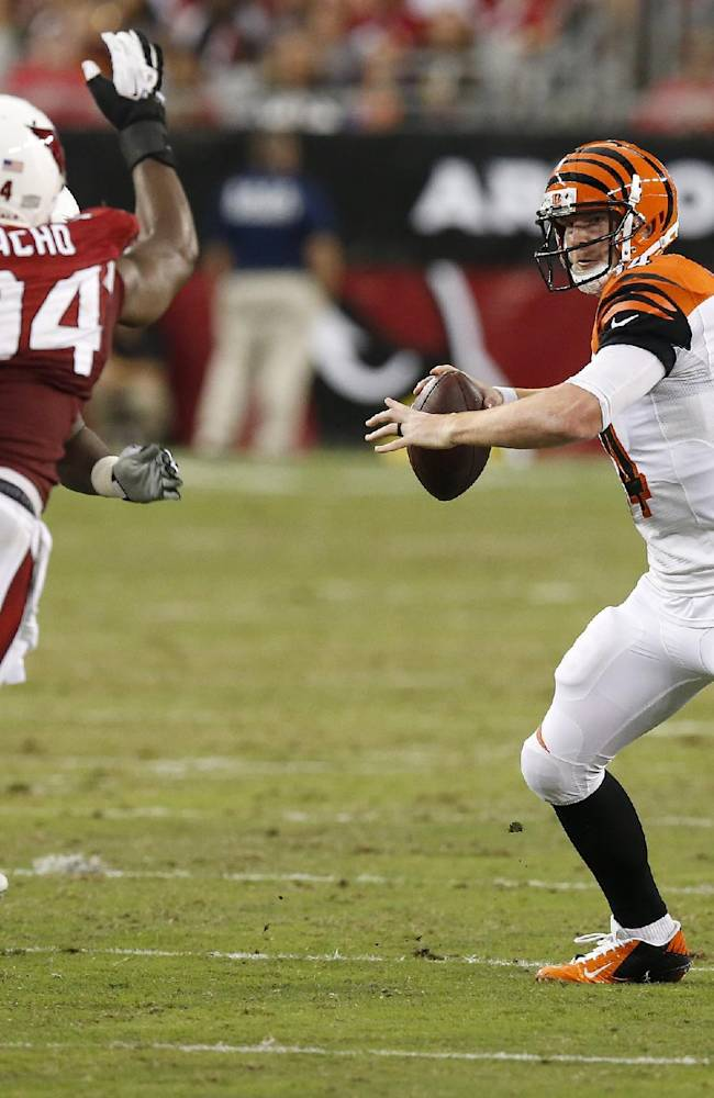 Cincinnati Bengals' Andy Dalton, right, scrambles away from Arizona Cardinals' Sam Acho (94) during the first half of an NFL preseason football game Sunday, Aug. 24, 2014, in Glendale, Ariz