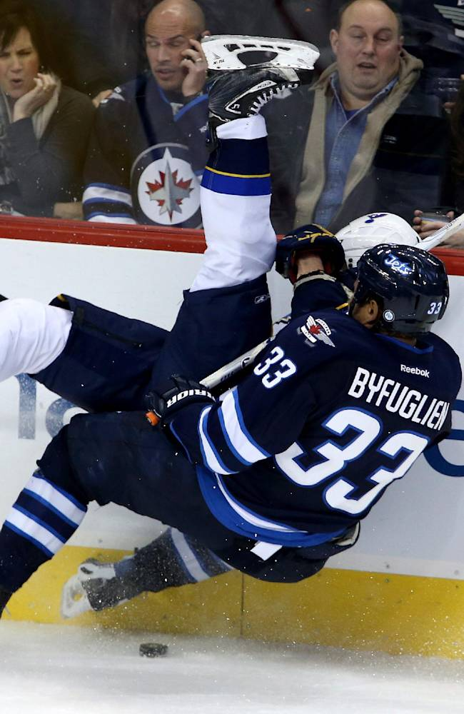 Winnipeg Jets' Dustin Byfuglien (33) trips St. Louis Blues' Vladimir Sobotka (17) during third period NHL hockey action in Winnipeg, Tuesday, Dec. 10, 2013. The Blues would score the game winning goal on the power play that followed