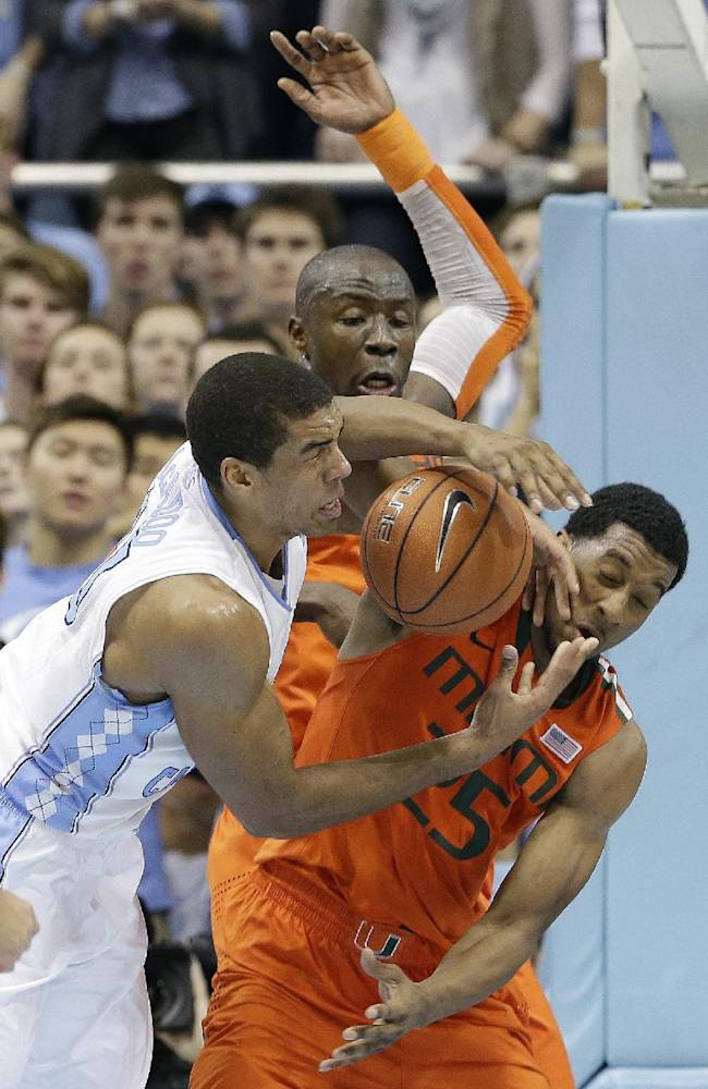 North Carolina's James Michael McAdoo, left, struggles for possession of the ball with Miami's Tonye Jekiri, rear, and Garrius Adams during the second half of an NCAA college basketball game in Chapel Hill, N.C., Wednesday, Jan. 8, 2014. Miami won 63-57