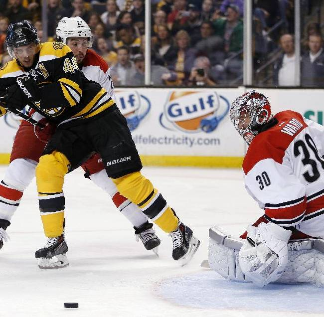 Boston Bruins' David Krejci (46) looks for the rebound after his shot on Carolina Hurricanes' Cam Ward (30) as Justin Faulk (27) defends in the second period of an NHL hockey game in Boston, Saturday, March 15, 2014