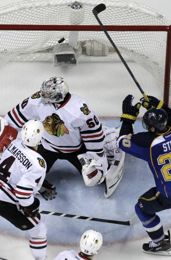 St. Louis Blues' Alexander Steen (20) scores the game-winning goal past Chicago Blackhawks goalie Corey Crawford and Niklas Hjalmarsson (4) during the third overtime in Game 1 of a first-round NHL hockey Stanley Cup playoff series Thursday, April 17, 2014, in St. Louis. The Blues won 4-3 in triple overtime