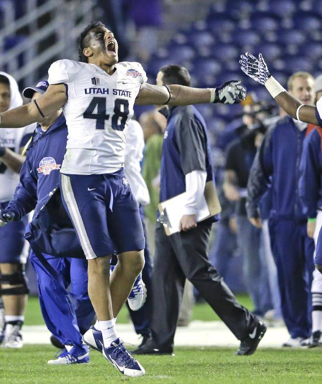 Utah State's Paul Piukala leads the celebration at the conclusion of State's 21-14 victory over Northern Illinois in the Poinsettia Bowl NCAA college football game Thursday, Dec. 26, 2013, in San Diego