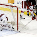 New Jersey Devils center Adam Henrique (14) scores a goal on Phoenix Coyotes goalie Thomas Greiss (1), of Germany, during the third period of an NHL hockey game, Thursday, March 27, 2014, in Newark, N.J. The Coyotes won 3-2 in a shootout The Associated Pr