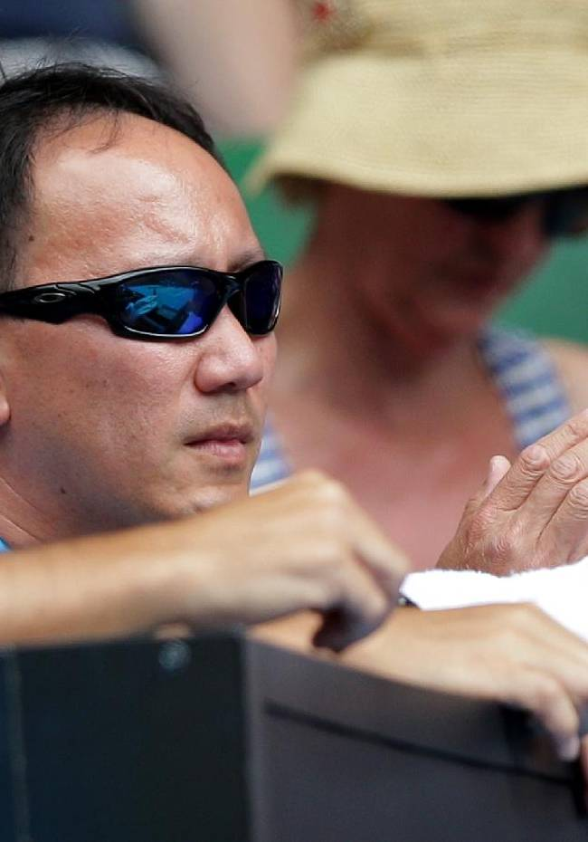 Former Grand Slam champion and coach of Japan's Kei NIshikori, Michael Chang watches Nishikori play Rafael Nadal of Spain in their fourth round match at the Australian Open tennis championship in Melbourne, Australia, Monday, Jan. 20, 2014