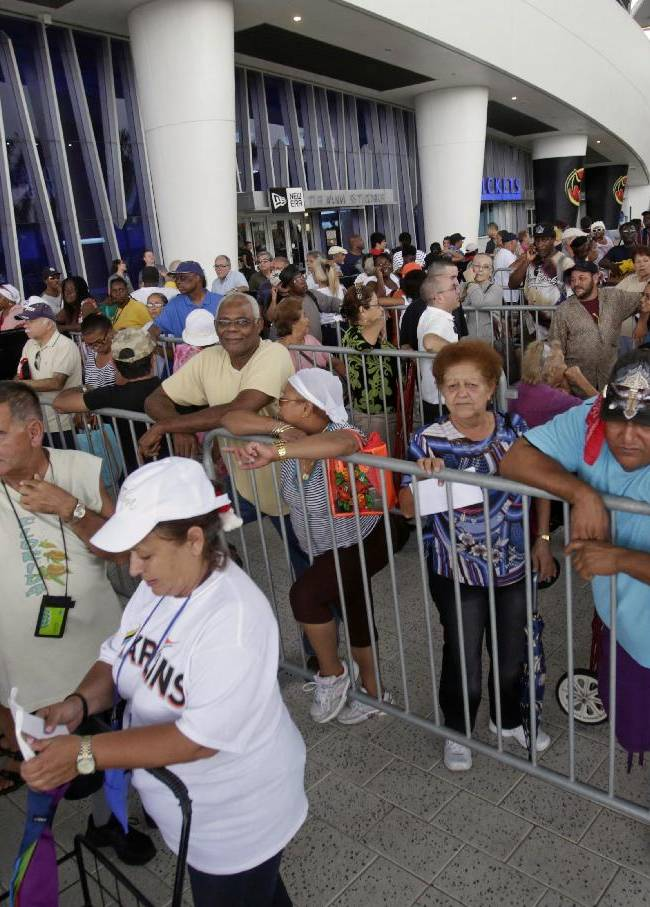 Local residents wait to receive goods during fifth annual Miami Marlins Ayudan Turkey Distribution at Marlins Park, Friday, Nov. 22, 2013, in Miami. The  Marlins and sponsors distributed 1,000 turkeys and Thanksgiving Day fixings to ballpark neighbors