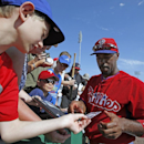 Philadelphia Phillies' Jimmy Rollins, right, autographs a baseball trading card for a young fan before a spring exhibition baseball game in Clearwater, Fla., Monday, March 10, 2014 The Associated Press