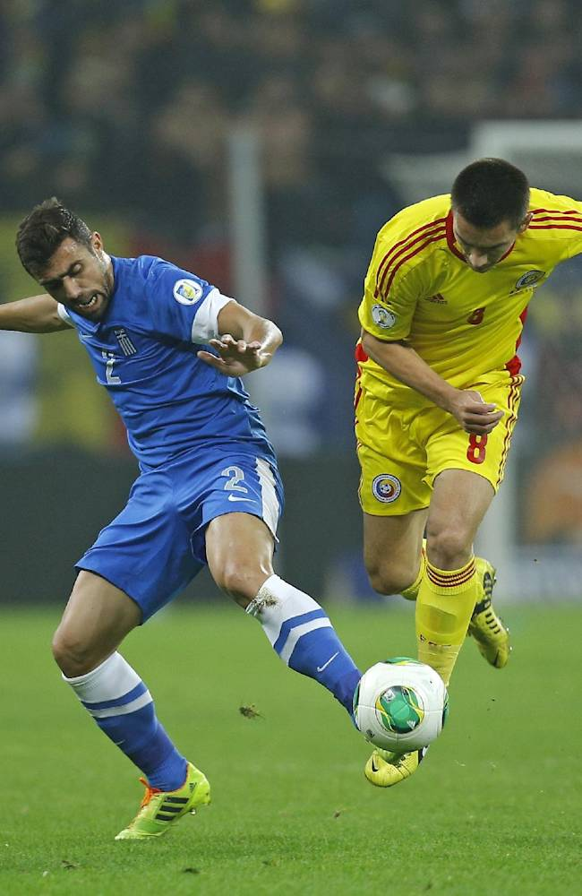 Greece's Yiannis Maniatis, left, and Romania's Ovidiu Hoban challenge for the ball during their World Cup qualifying playoff second leg soccer match at the National Arena in Bucharest, Tuesday, Nov. 19, 2013