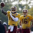 Washington Redskins quarterback Robert Griffin III, left, passes as quarterback Colt McCoy looks on, during practice at the team's NFL football training facility, Saturday, July 26, 2014 in Richmond, Va The Associated Press