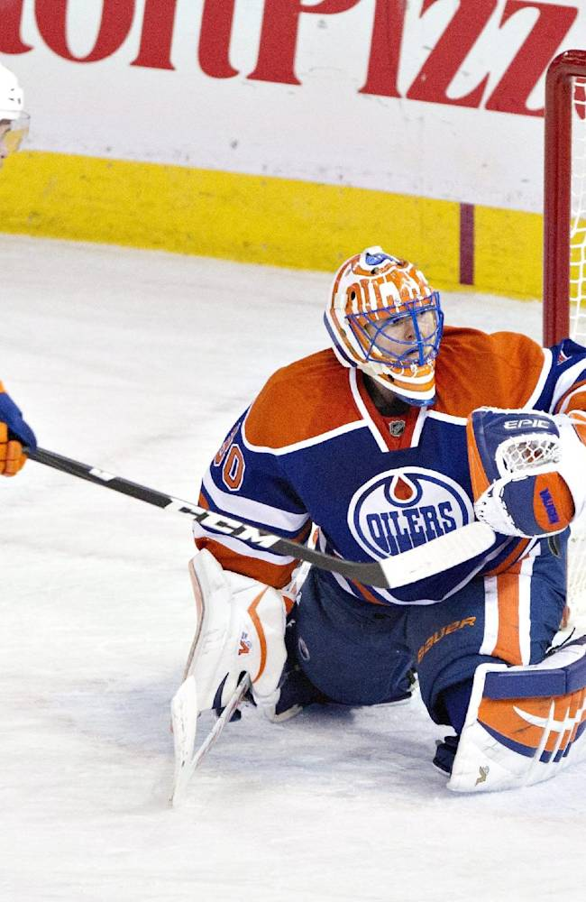 New York Islanders' Michael Grabner (40) hits the post as Edmonton Oilers goalie Ben Scrivens (30) tries to make the save during third period NHL hockey action in Edmonton, Alberta, on Thursday March 6, 2014