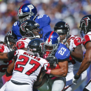 New York Giants running back Rashad Jennings (23) is tackled by several Atlanta Falcons players during the first half of an NFL football game, Sunday, Oct. 5, 2014, in East Rutherford, N.J The Associated Press