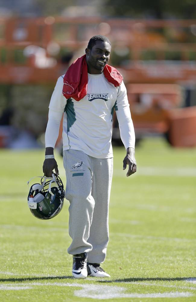 Philadelphia Eagles quarterback Michael Vick walks to a news conference after practice at the NFL football team's training facility, Tuesday, Oct. 15, 2013, in Philadelphia